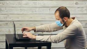 Ένα άτομο σε μια ιατρική εργασία μασκών στον υπολογιστή και τους βήχες φιλμ μικρού μήκους