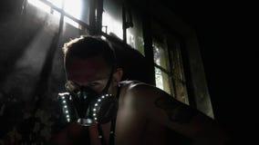 Ένα άτομο σε μια καμμένος μάσκα αερίου εξετάζει το σπασμένο παράθυρο απόθεμα βίντεο