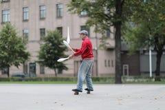 Ένα άτομο σε μια ΚΑΠ κάνει ταχυδακτυλουργίες με τις λέσχες στην οδό στοκ φωτογραφία