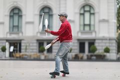 Ένα άτομο σε μια ΚΑΠ κάνει ταχυδακτυλουργίες με τις λέσχες στην οδό στοκ φωτογραφία με δικαίωμα ελεύθερης χρήσης