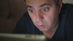 Ένα άτομο σε μια μπλε μπλούζα σε ένα σκοτεινό δωμάτιο που βρίσκεται στον καναπέ που προσέχει μια ηλεκτρονική ταμπλέτα Φόβος και έ απόθεμα βίντεο