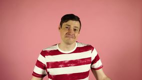 Ένα άτομο σε μια ριγωτή μπλούζα σε ένα ρόδινο υπόβαθρο Να φανεί κάμερα λέει ναι απόθεμα βίντεο