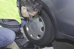 Ένα άτομο σε μια φανέλλα ασφάλειας επισκευάζει ένα αυτοκίνητο Στοκ φωτογραφίες με δικαίωμα ελεύθερης χρήσης