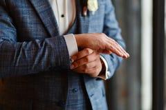 Ένα άτομο σε ένα μοντέρνο κοστούμι ισιώνει τις μανσέτες στο πουκάμισό του Πυροβολισμός ενός επιχειρηματία σε ένα κοστούμι χρυσή ι στοκ εικόνες με δικαίωμα ελεύθερης χρήσης
