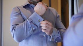 Ένα άτομο σε ένα μπλε πουκάμισο στερεώνει τα μανικετόκουμπά του στο πο φιλμ μικρού μήκους