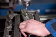 Ένα άτομο σε ένα μπλε πουκάμισο τρυπά μια τρύπα στις λεπτομέρειες με τρυπάνι σε μια μικρή επιχείρηση Στοκ Φωτογραφία