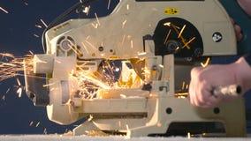 Ένα άτομο σε ένα μπλε υπόβαθρο χωρίζει την κινηματογράφηση σε πρώτο πλάνο σωλήνων μετάλλων με 4K τους σπινθήρες απόθεμα βίντεο