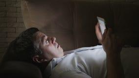 Ένα άτομο σε ένα σκοτεινό δωμάτιο, που βρίσκεται στην πλάτη του στον καναπέ, εξετάζει την ηλεκτρονική ταμπλέτα Φόβος και έκπληξη  φιλμ μικρού μήκους