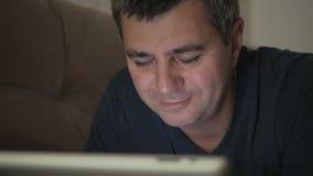 Ένα άτομο σε ένα σκοτεινό δωμάτιο που βρίσκεται σε ένα χαμόγελο καναπέδων που εξετάζει μια ηλεκτρονική ταμπλέτα Συγκινήσεις στο π απόθεμα βίντεο