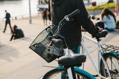 Ένα άτομο στέκεται δίπλα σε ένα ποδήλατο σε έναν χώρο στάθμευσης ποδηλάτων στο ανάχωμα στο Βερολίνο Θολωμένοι άνθρωποι στο υπόβαθ Στοκ Εικόνες
