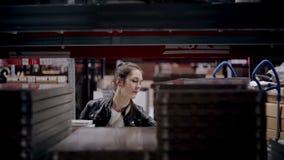 Ένα άτομο στέκεται κοντά στα ράφια με τα αγαθά στα κουτιά από χαρτόνι και ελέγχει τον κατάλογό του σε μια αποθήκη εμπορευμάτων απόθεμα βίντεο