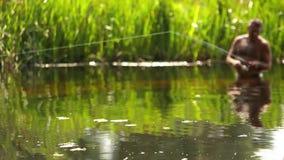 Ένα άτομο στέκεται μέση-βαθιά στο νερό και ρίχνει μια γραμμή στα ψάρια σύλληψης φιλμ μικρού μήκους