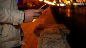 Ένα άτομο στέκεται στην προκυμαία και χρησιμοποιεί το τηλέφωνο τη νύχτα σε ένα κλίμα των φω'των νύχτας 4k, θαμπάδα υποβάθρου απόθεμα βίντεο