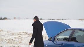 Ένα άτομο στέκεται στο χειμερινό δρόμο, καλεί το ένα τηλέφωνο και ζητά τη βοήθεια φιλμ μικρού μήκους
