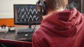 Ένα άτομο στα ακουστικά που κάθονται από τον υπολογιστή στο στούντιο υγιούς καταγραφής και που καταγράφουν ένα τραγούδι απόθεμα βίντεο