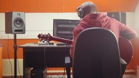 Ένα άτομο στα ακουστικά που κάθονται από τον υπολογιστή στο στούντιο και που καταγράφουν ένα τραγούδι απόθεμα βίντεο