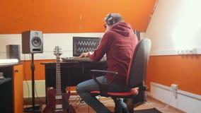 Ένα άτομο στα ακουστικά που παίζει την κιθάρα στο στούντιο υγιούς καταγραφής φιλμ μικρού μήκους