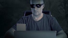 Ένα άτομο στα γυαλιά και μια μπλούζα τη νύχτα σε έναν πίνακα με ένα lap-top Ο χάκερ ολοκλήρωσε την υποχρέωση και αφαίρεσε τις αυτ φιλμ μικρού μήκους