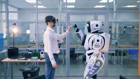 Ένα άτομο στα εικονικά γυαλιά και ένα ρομπότ δίνουν σε μεταξύ τους υψηλός-πέντε απόθεμα βίντεο