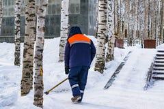 Ένα άτομο στα ενδύματα εργασίας με ένα φτυάρι αφαιρεί το χιόνι από τη διαδρομή στο πάρκο στοκ εικόνες