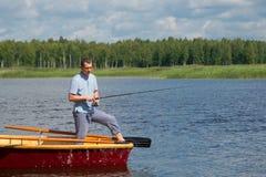 Ένα άτομο στα κίτρινα γυαλιά, σε μια βάρκα με τα κουπιά, στο κέντρο της λίμνης, κρατά έναν πόλο αλιείας για να πιάσει ένα μεγάλο  στοκ εικόνα