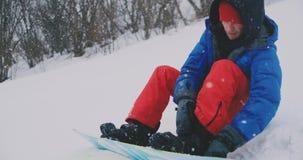 Ένα άτομο στα κόκκινα εσώρουχα που κάθεται στο χιόνι στερεώνει τις μπό απόθεμα βίντεο