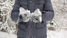 Ένα άτομο στα μαύρα γάντια πήρε το χιόνι στα χέρια του snowflakes πέφτουν και πέφτουν φιλμ μικρού μήκους