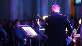Ένα άτομο στα τύμπανα παιχνιδιού κοστουμιών και εξέταση τις σημειώσεις στη συναυλία τζαζ υποστηρίξτε την όψη φιλμ μικρού μήκους