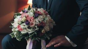 Ένα άτομο στα χέρια του που κρατά μια όμορφη ανθοδέσμη των λουλουδιών απόθεμα βίντεο