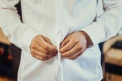 Ένα άτομο στερεώνει τα κουμπιά στο πουκάμισό του στοκ εικόνα