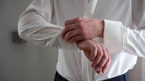 Ένα άτομο στερεώνει τα μανικετόκουμπα σε ένα άσπρο πουκάμισο φιλμ μικρού μήκους