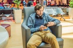 Ένα άτομο στην περιοχή σαλονιών στον αερολιμένα περιμένει το αεροπλάνο του, χρησιμοποιεί ένα smartphone και τα ακουστικά χαμογελώ στοκ εικόνα