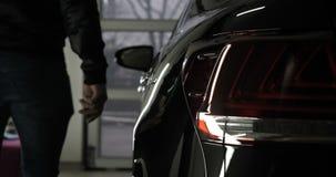 Ένα άτομο στην υπηρεσία αυτοκινήτων γκαράζ ελέγχει το συναγερμό αυτοκινήτων και πηγαίνει έπειτα μακριά φιλμ μικρού μήκους