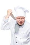 Ένα άτομο στους αρχιμάγειρες κοστουμιών με ένα αιχμηρό μαχαίρι σε ένα λευκό Στοκ Φωτογραφίες