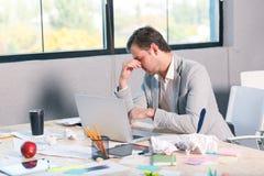 Ένα άτομο στο γραφείο του με ένα lap-top και τσαλακωμένα έγγραφα, και λόγω της αποτυχίας κρατά το κεφάλι του Στοκ φωτογραφία με δικαίωμα ελεύθερης χρήσης