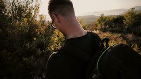 Ένα άτομο στο ηλιοβασίλεμα ανέρχεται σε ένα βουνό με ένα σακίδιο πλάτης απόθεμα βίντεο