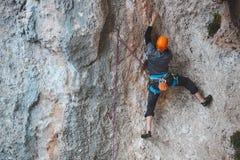 Ένα άτομο στο κράνος αναρριχείται στο βράχο Στοκ Εικόνα