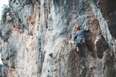 Ένα άτομο στο κράνος αναρριχείται στο βράχο Στοκ Φωτογραφίες