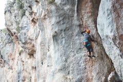 Ένα άτομο στο κράνος αναρριχείται στο βράχο Στοκ Εικόνες