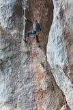 Ένα άτομο στο κράνος αναρριχείται στο βράχο Στοκ εικόνα με δικαίωμα ελεύθερης χρήσης
