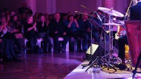 Ένα άτομο στο παιχνίδι κοστουμιών παίζει τύμπανο στη συναυλία τζαζ Το ακροατήριο που χτυπά τα χέρια τους απόθεμα βίντεο