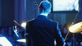 Ένα άτομο στο παιχνίδι κοστουμιών παίζει τύμπανο στη συναυλία τζαζ υποστηρίξτε την όψη φιλμ μικρού μήκους