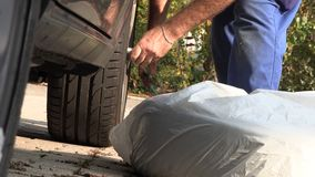 Ένα άτομο στο παντελόνι εργασίας αντικαθιστά μια ρόδα αυτοκινήτων, σε αργή κίνηση απόθεμα βίντεο