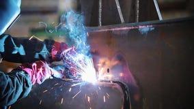 Ένα άτομο στο προστατευτικό εργαλείο ενώνει στενά το μέταλλο με έναν φανό απόθεμα βίντεο