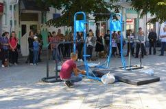Ένα άτομο στο τετράγωνο κάνει τις γυμναστικές ασκήσεις στους ανώμαλους φραγμούς στοκ εικόνα με δικαίωμα ελεύθερης χρήσης