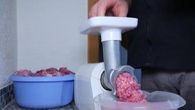 Ένα άτομο στρίβει το κρέας χοιρινού κρέατος σε ένα ηλεκτρικό μηχανή κοπής κιμά απόθεμα βίντεο
