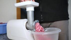 Ένα άτομο στρίβει το κρέας χοιρινού κρέατος σε ένα ηλεκτρικό μηχανή κοπής κιμά φιλμ μικρού μήκους