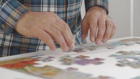 Ένα άτομο συλλέγει τους μεγάλους γρίφους στον πίνακα στο διαμέρισμα φιλμ μικρού μήκους