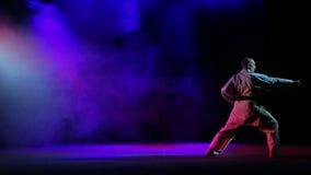 Ένα άτομο συμμετέχει karate σε ένα υπόβαθρο του χρωματισμένου καπνού απόθεμα βίντεο