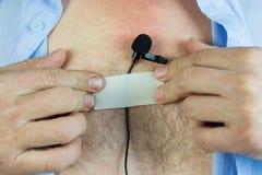 Ένα άτομο συνδέει ένα κρυμμένο μικρόφωνο με το στήθος του με μια κολλητική ταινία Στοκ φωτογραφία με δικαίωμα ελεύθερης χρήσης